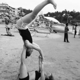 Christina Liljeroth acro yoga on beach smiling